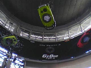 円筒形の建物の中.壁面にポスター,天井に宙づりの模型.