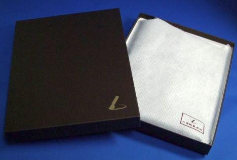 土屋鞄製造所の焦げ茶の箱を開けると,製品が不織布に包まれている.