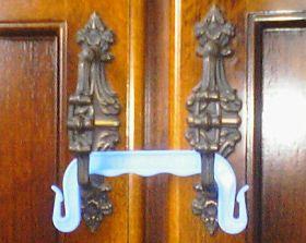 観音開きの戸棚の取っ手に荷造りしたときに紐に引っかけて使う持ち手をはめてあります.